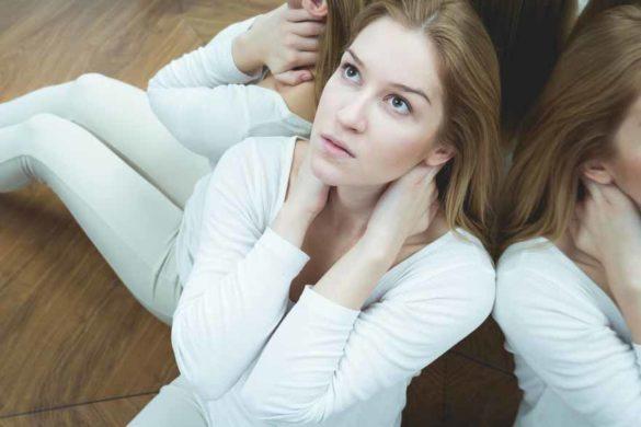 Eine ängstliche Frau sitzt in einer Ecke mit verspiegelten Wänden und starrt in die Leere.