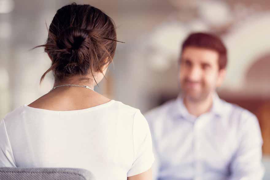 Eine Bewerberin sitzt mit dem Rücken zum Betrachter beim Vorstellungsgespräch.