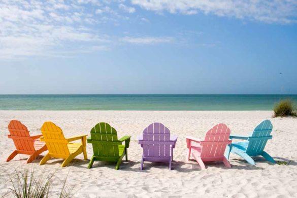 Fünf bunte Liegestühle am Strand mit Blick aufs Meer.