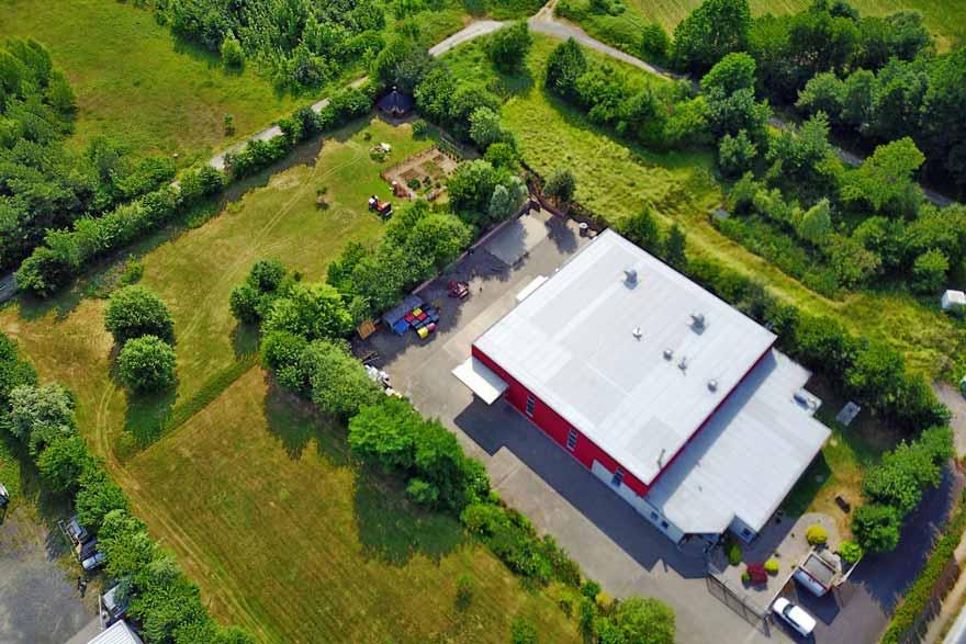 Dronenaufnahme einer Lagerhalle in einem ländlichen Industriegebiet.