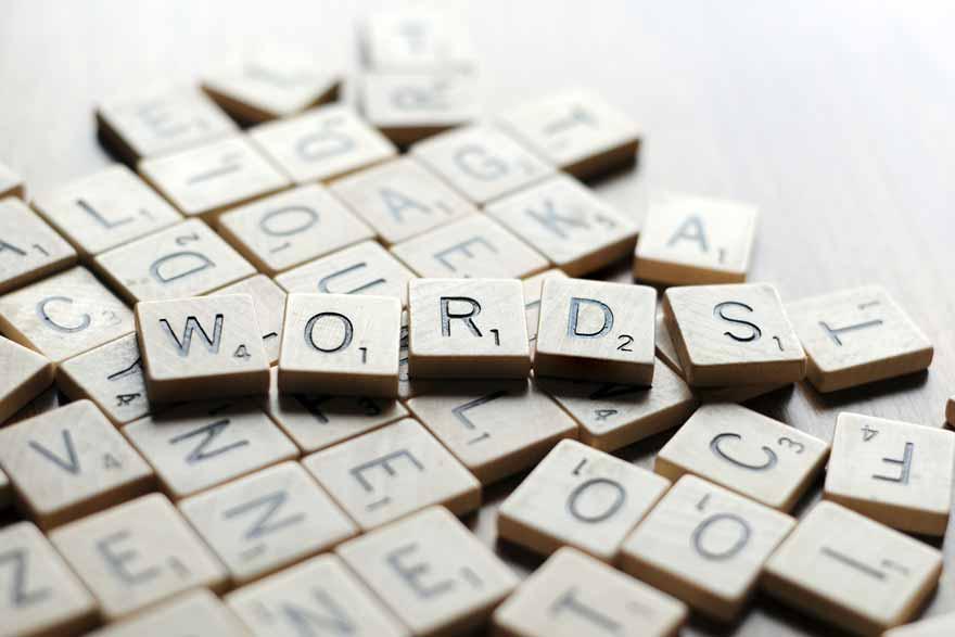 """Ein Häufchen Scrabble-Spielsteine. GAnz oben liegt eine Buchstabenreihe die das Wort """"WORDS"""" ergibt."""