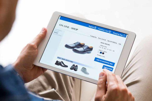 Ein Mann kauft online Schuhe mit einem Tablet.
