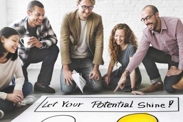 """Eine Gruppe lachender Personen zeigt auf ein Banner am Boden auf dem steht: """"Let your Potential Shine""""."""