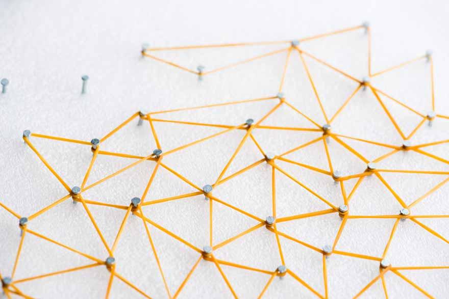 Eine gelbe Schnur schlängelt sich durch unregelmäßig eingeschlagene Nägel um ein Netzwerk darzustellen.