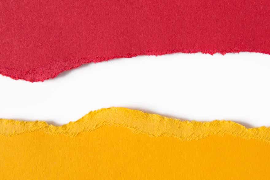 Gelbes und rotes Papier angerissen liegen auf weißem Grund.