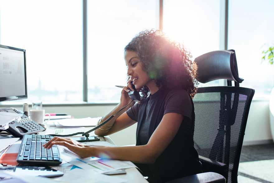 Eine Geschäftsfrau telefoniert und tippt bei der Arbeit in ihrem Büro.