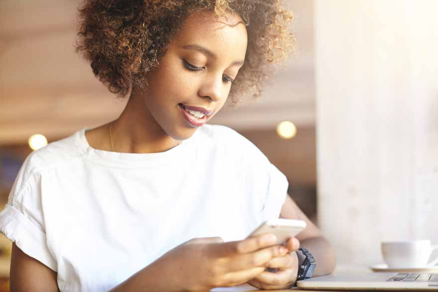 Junge Bewerberin checkt ihr LinkedIn Profil am Smartphone.