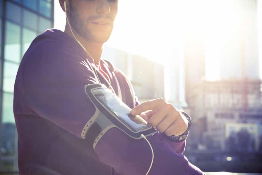 Ein junger Mann nutzt sein Smartphone am Arm als Mp3-Player beim Joggen.