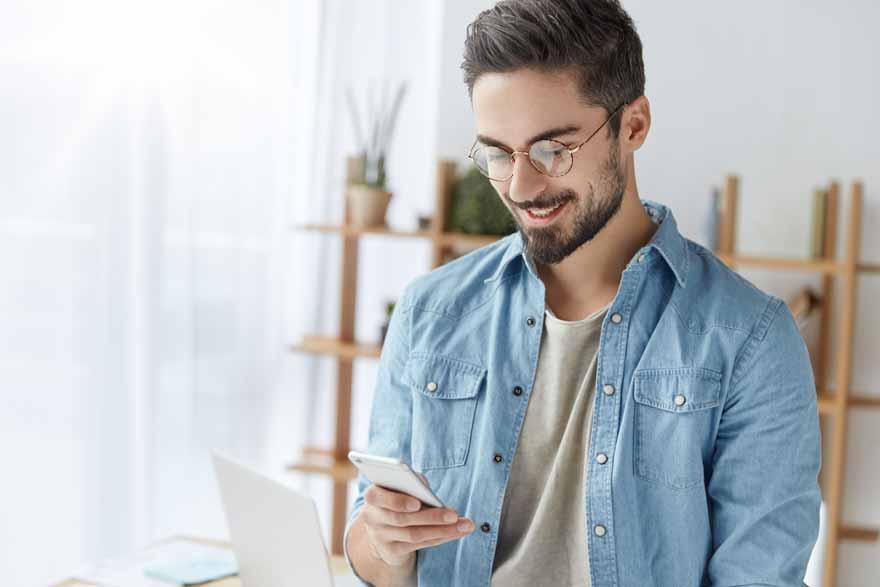 Junger, bärtiger Mann mit Smartphone.