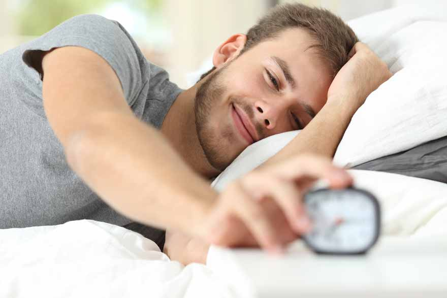 Junger Student liegt im Bett und drückt den Snooze-Knopf auf seinem Wecker.