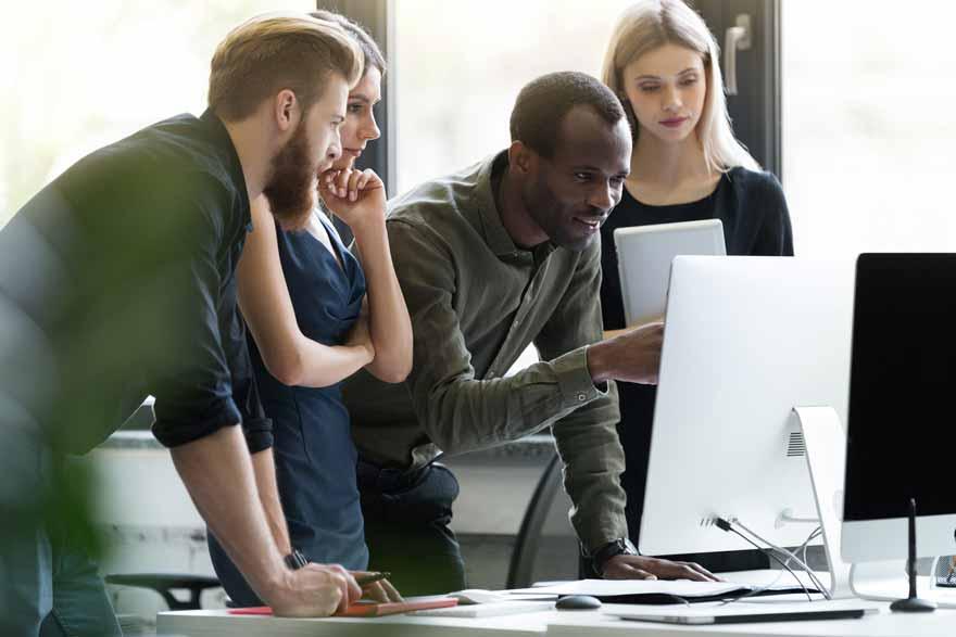 Eine Gruppe von vier Mitarbeitern bei einem gemeinsamen Projekt.