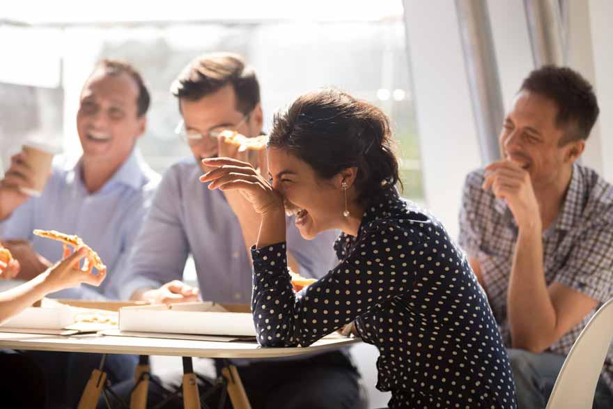 Fröhliche Mitarbeiter lachen und essen gemeinsam Pizza in der Mittagspause.