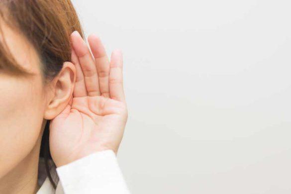 Eine Mitarbeiterin hält eine Hand an ihr Ohr um besser hören zu können.