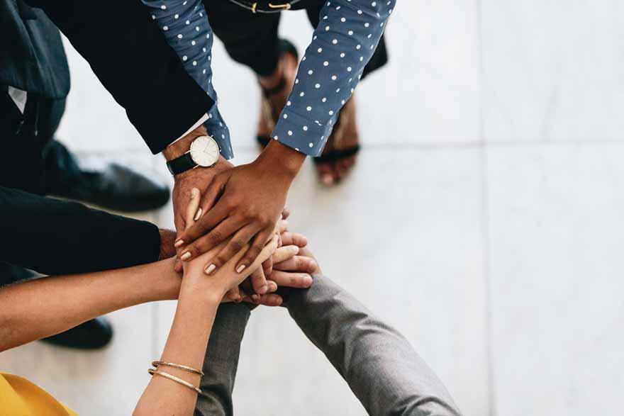 Mehrere Personen stehen im Kreis und legen die Hände übereinander.