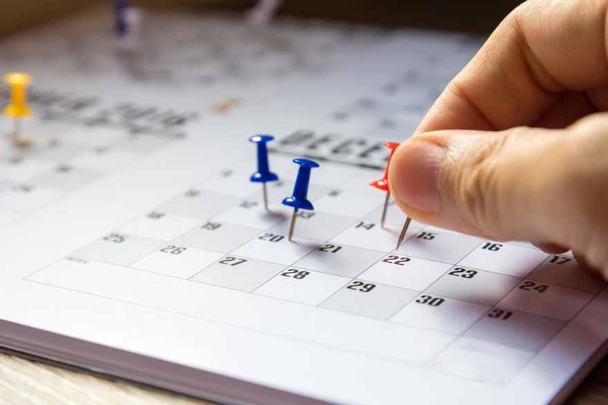Mehrere Pins die in einen Kalender gesteckt werden.