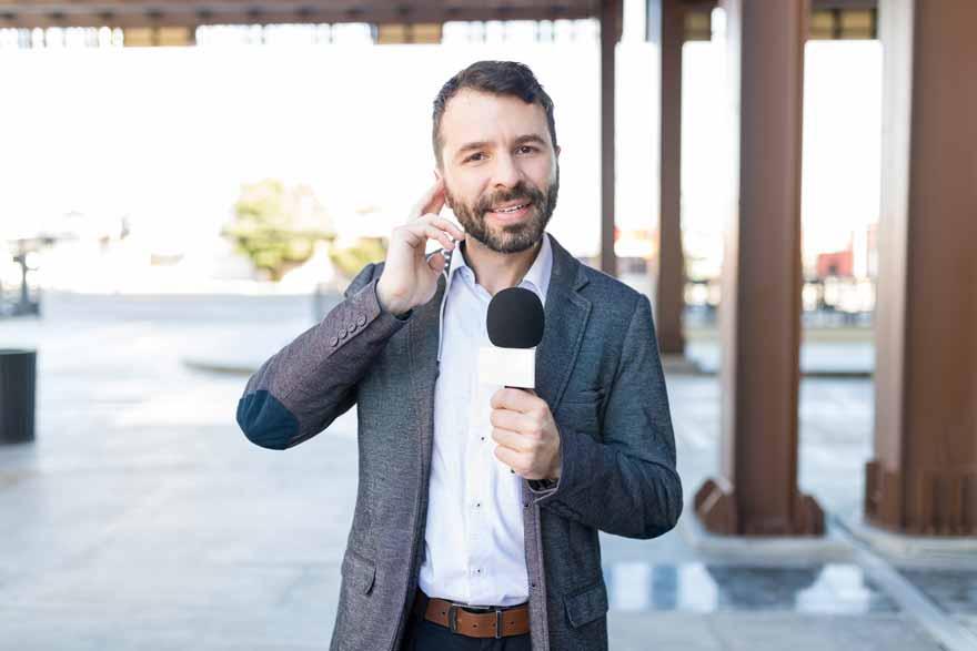 Reporter mit Mikrofon spricht in die Kamera.
