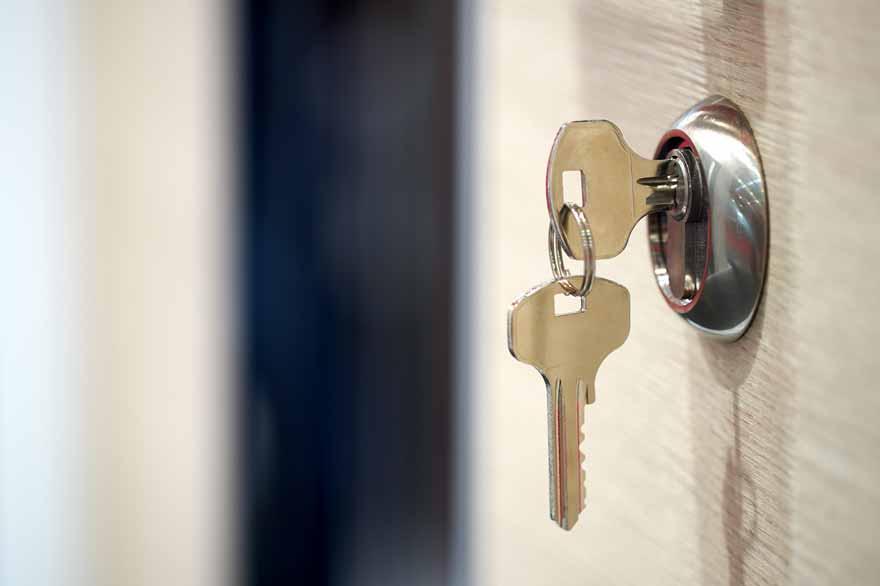 Ein Schlüssel steckt im Schlüsselloch einer Tür.
