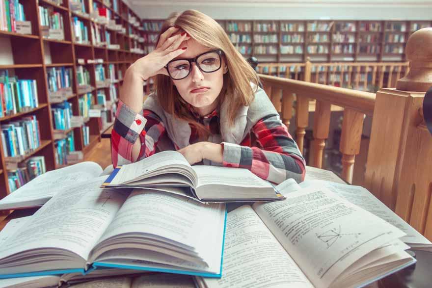 Studentin sitzt nachdenklich in der Bibliothek über ihren Büchern.