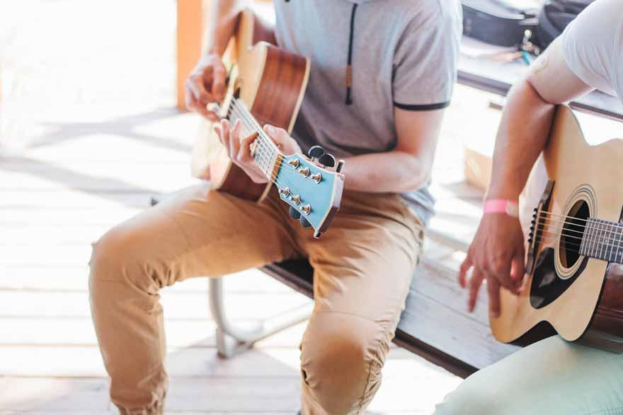 Zwei Mitarbeiter spielen Gitarre.