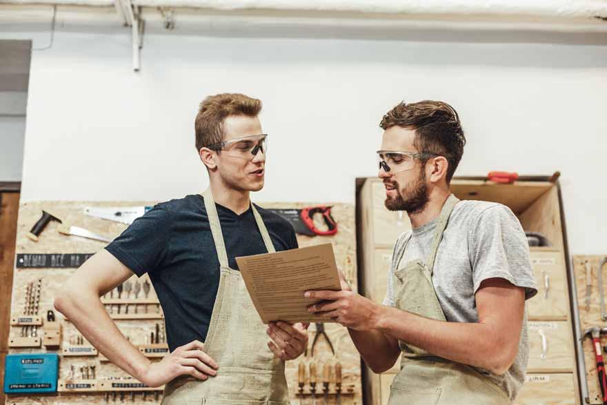 Zwei Hobbyschreiner unterhalten sich in einer Schreiner Werkstatt.