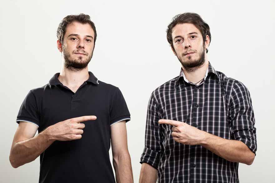 Zwei Zwillinge zeigen mit dem Zeigefinger aufeinander.