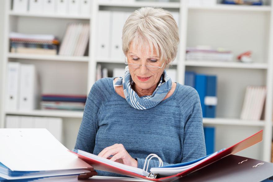 Ältere Mitarbeiterin betrachtet Dokumente in einem von mehreren Ordnern