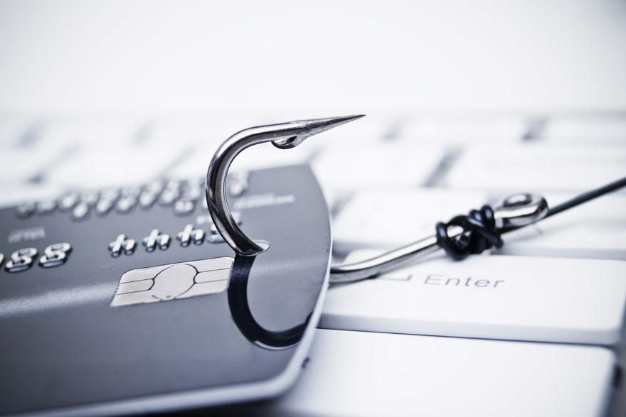Silberner Angelhaken greift eine Kreditkarte auf weißer Tastatur