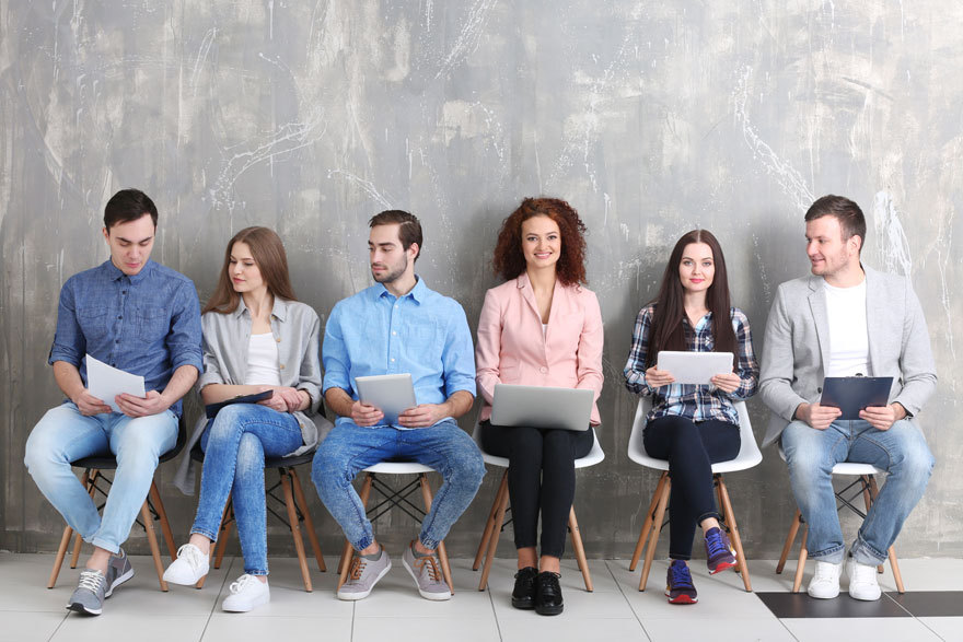 Sechs junge Bewerber sitzen nebeneinander und warten auf ihre Vorstellungsgespräche