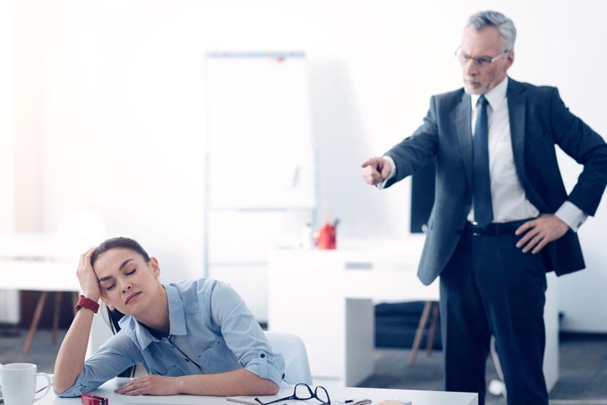 Boss steht mit ausgestrecktem Zeigefinger und bösem Blick hinter einer am Schreibtisch sitzenden und unglücklich guckenden Mitarbeiterin