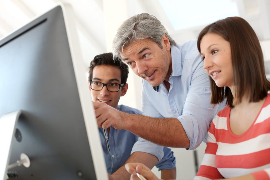 Mann mittleren Alters zeigt jungen Nachwuchskräften etwas am Computer