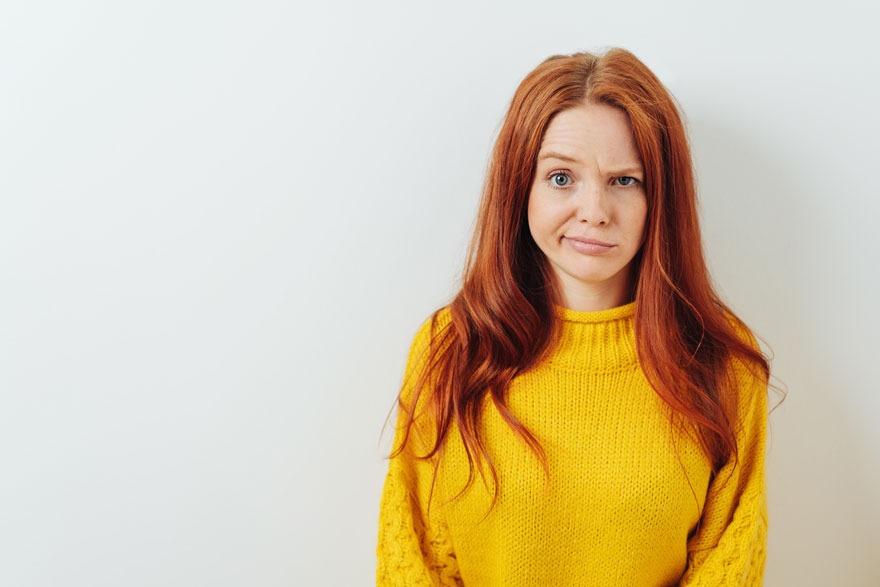 Frau in gelbem Strickpullover steht vor einer weißen Wand und blickt fragend in die Kamera