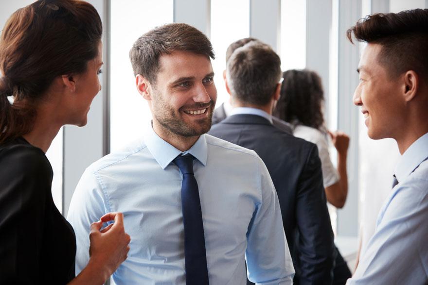 Drei Geschäftsleute unterhalten sich in einem Raum mit weiteren Personen freundlich