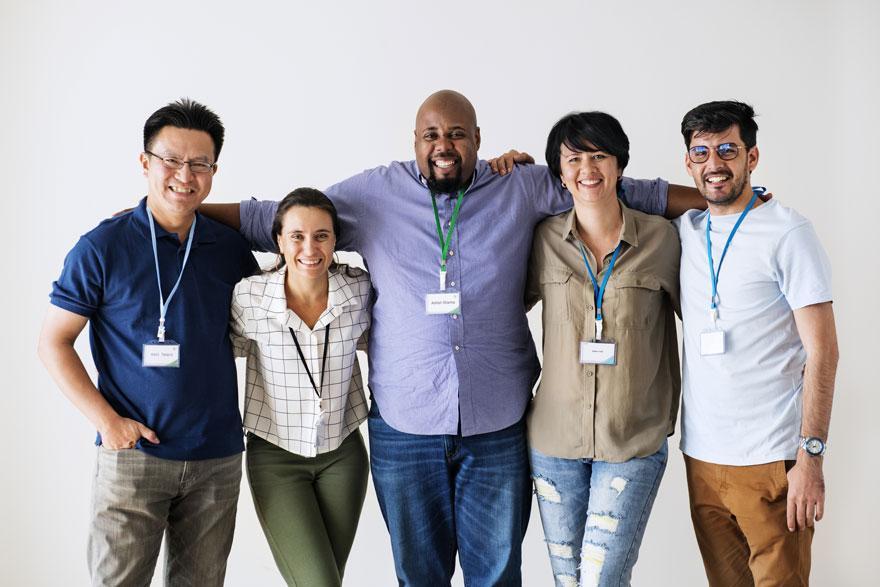 Fünf Kollegen unterschiedlicher Herkunft posieren für ein Gruppenbild