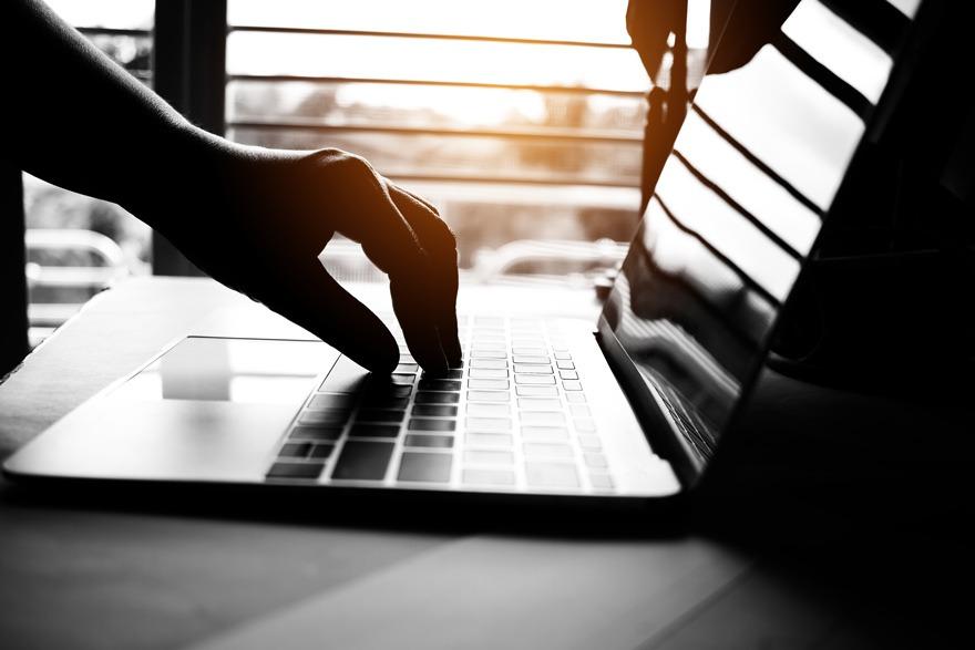 Hand drückt Tastenkombination auf Laptop