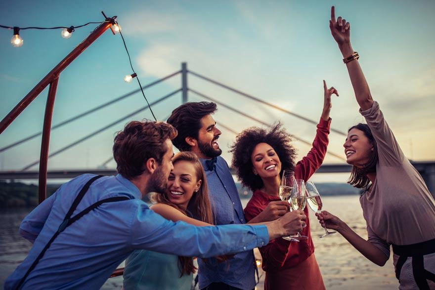 Junge Menschen feiern ausgelassen an einer Brücke mit Sekt in der Hand