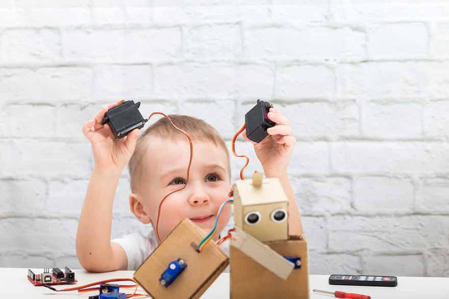 Ein kleiner Junge baut sich einen Roboter.