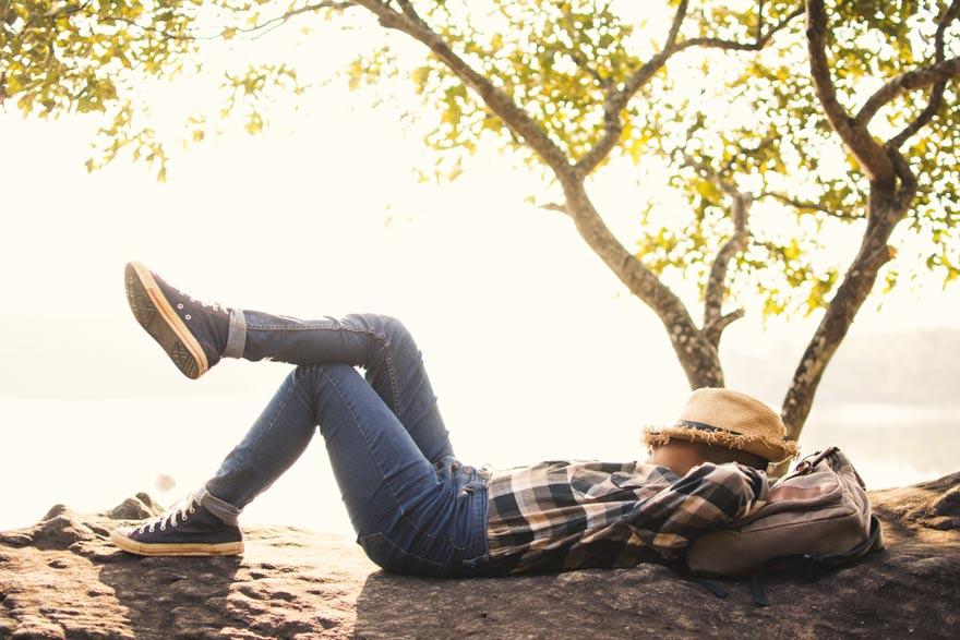 Mann mit Hut liegt in der Sonne und ruht sich aus