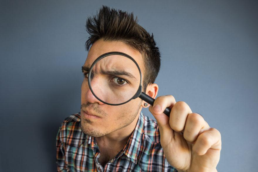 Mann im karierten Hemd blickt mit dem linken Auge durch eine Lupe