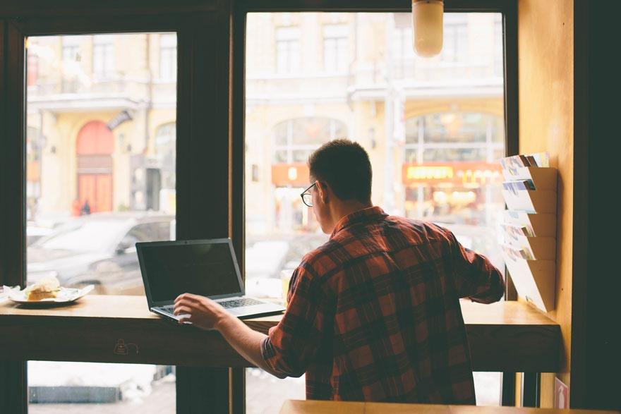 Mann sitzt an einer Fenstertheke im Café und nutzt mit seinem Laptop das kostenlose WLAN um anonym im Netz zu surfen