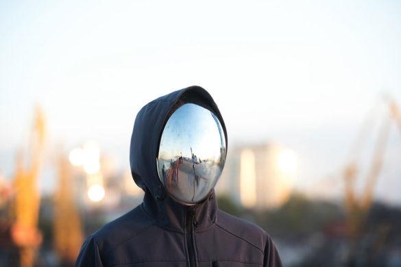 Mit verspiegelter Maske und schwarzer Kapuzenjacke verhüllte Person