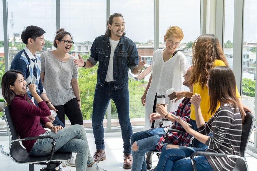 Multiethnisches Team sitzt und steht in einem Kreis und lacht fröhlich