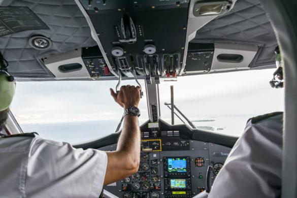 Over-Shoulder-Aufnahme zweier Piloten im Cockpit eines Flugzeugs