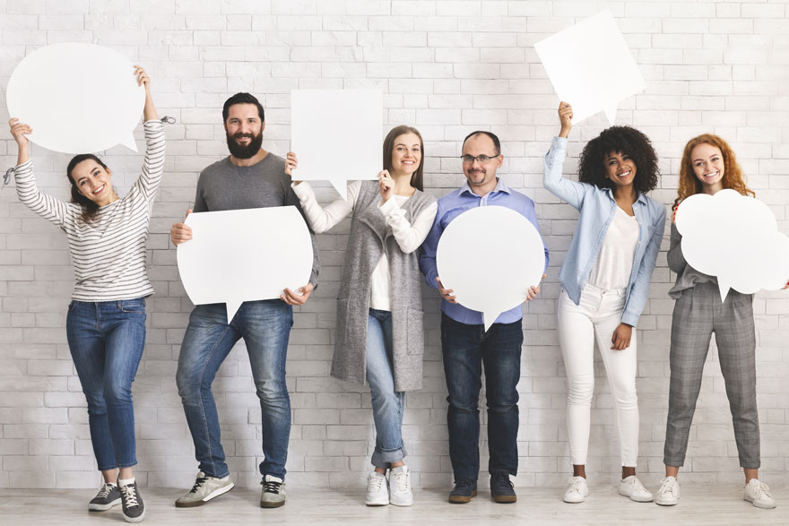 Sechs ganz unterschiedliche Personen stehen nebeneinander und halten große Sprechblasen aus weißem Papier in den Händen