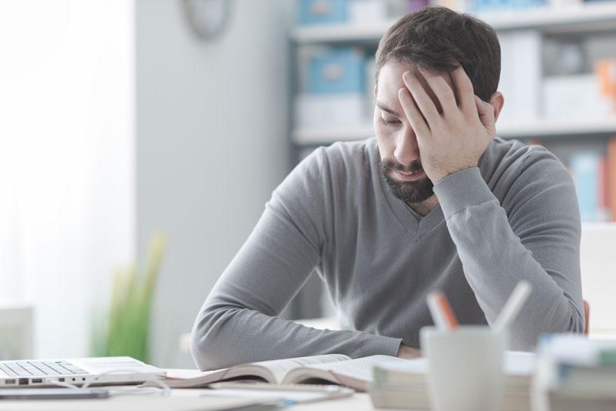 Frustrierter Student mit linker Hand am Kopf versucht über ein Buch gebeugt zu lernen