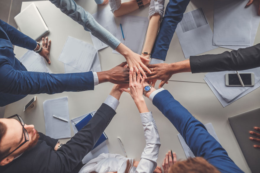Team feiert die gemeinsame Teamarbeit durch zusammenstecken der Hände über einem Tisch