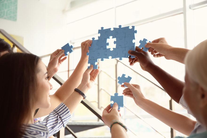 Teammitglieder bauen ihre Puzzleteile in der Luft an ein gemeinsames Puzzle und verdeutlichen so ihre Teamarbeit