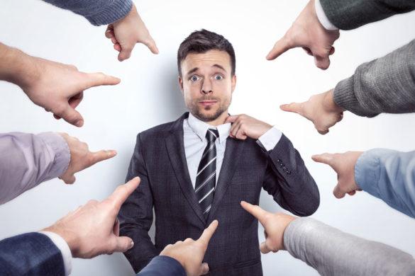 Verschiedene Zeigefinger zeigen tadelnd auf einen nervösen Geschäftsmann in der Mitte