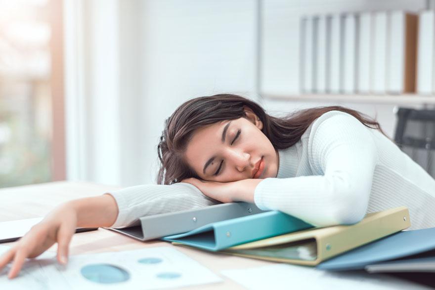 Junge Frau ist von der Arbeit erschöpft und schläft über ihren Schreibtisch gebeugt auf vor ihr liegenden Ordnern