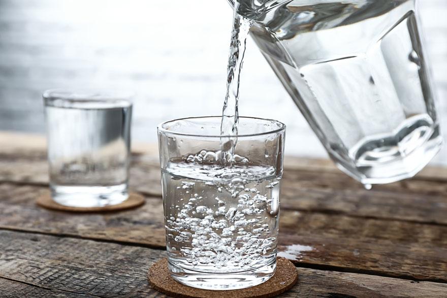 Wasserkaraffe füllt zwei Gläser auf einem Holztisch mit Wasser
