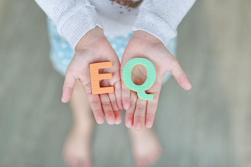 Zwei Kinderhände präsentieren mit nach oben gekehrten Handflächen die Buchstaben EQ aus Moosgummi. EQ steht für Emotionale Intelligenz.